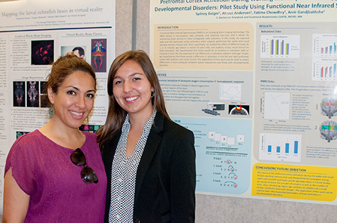 Sydney Geiger '18 (right) and National Institutes of Health biomedical engineer Afrouz Anderson stand in front of a poster describing the research they worked on together using emerging brain imaging technology.