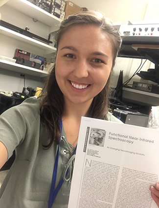 Sydney Geiger '18 in her National Institutes of Health lab with some of the research available on Functional Near-Infrared Spectroscopy.